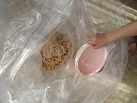 潰した大豆を袋に入れていく