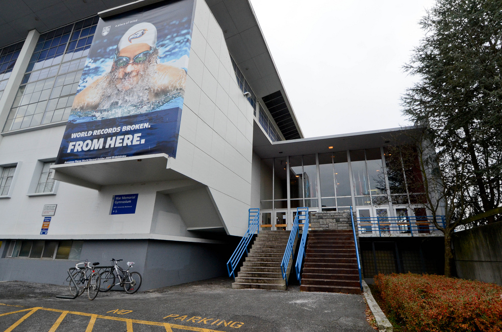 The UBC War Memorial Gym. The electrical conduit goes from the top of the stairs to the sub-roof above the doors, and is barely visible behind the tree on the right. The overhanging roof is the main feature above the subroof.