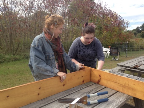 Two teen girls constructing a raised garden bed frame