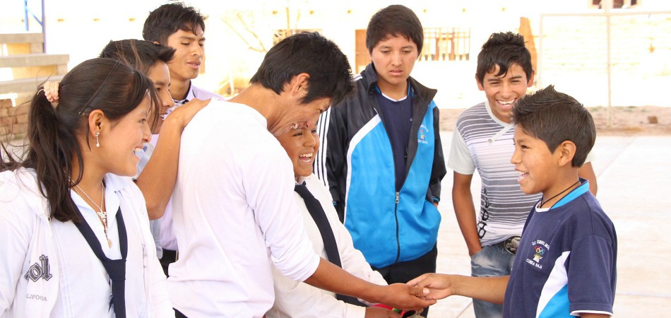 A student participates in a student government lottery in Bolivia. At this school, students draw different colored beans from a pot.