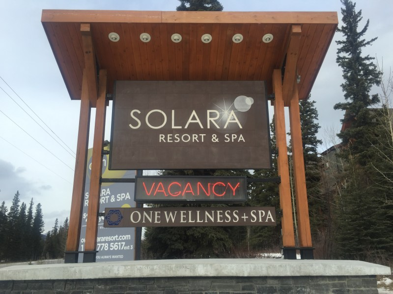 solara resort and spa and one wellness sign by craftsman house numbers at the entrance to
