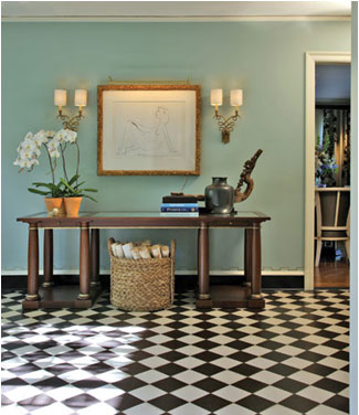 black slate-and-diamond tiles and a bold, decorative mirror-topped table