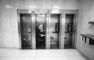Man in phone booth, NYC, ©David Carol
