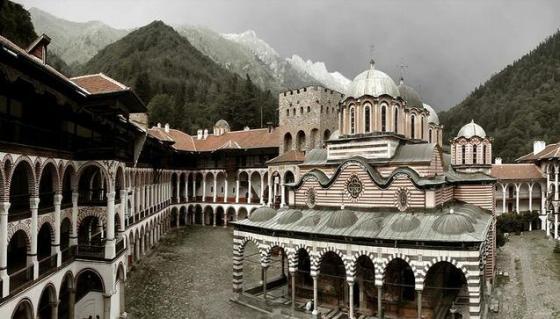 """Рилският манастир е създаден през 30-години на Хв. на мястото на старата постница в планина Рила. През времето на своето съществуване манастирът е бил многократно преустройван, разрушаван и отново възстановяван. Рилската обител е придобила сегашния си облик към средата на миналото столетие. Тя е най-голямата и най-почитаната българска обител. Счита се, че създателят на Рилската обител е първия български монах-отшелник Йоан Рилски. Рилският манастир е разположен на 1,147 метра надморска височина сред ухаещите иглолистни гори на планината Рила. Обителта представлява комплекс от култови, жилищни и стопански постройки с обща площ 8800 кв. м. Рилският манастир се отличава с уникална архитектура. Отвън, с 24-метровите каменни стени на основните си сгради, които образуват неправилен петоъгълник, манастирът има вид на крепост. Затова поклонникът или туристът, който попада във вътрешността през една от двете железни порти, остава изненадан от мекотата на архитектурните форми: арки и колонади, покрити дървени стълби и резбовани чардаци, зад които са килиите – 300-400 на брой. В средата на калдъръмения двор в странна симбиоза съжителстват суровите бойници на Хрельовата кула и бароковите сребърни куполи на главната църква. В средата на вътрешния двор се издига най-старата сграда в комплекса – впечатляваща каменна кула, създадена от местния феодал Севастократор Хрелю през 1334-1335 г. Непосредствено до нея стои и малка църква, която е само няколко години по-млада (1343 г.). В по-нови времена (1844 г.) към кулата е добавена и камбанария. Приблизително от същия период датира и главната манастирска черква """"Рождество Богородично"""". Архитект е майстор Петър Иванович, който работи по нея межу 1834 и 1837 г. Храма е 5-куполен, с три олтарни ниши и два странични параклиса. Едно от най-ценните неща вътре е иконостаса със своята невероятна дърворезба. Стенописите са завършени през 1846 г. и са дело на много майстори, но само известния Захари Зограф се е подписал под своите рисунки. В църкв"""