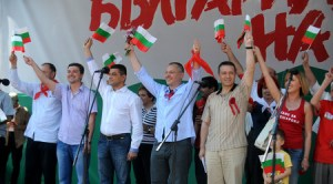 """27 юли 2013 г. Зам-председателката на парламента """"червената блондинка"""" Мая Манолова (най-дясно на снимката) бе облечена в потник, но ярко червен, с който се яви и на трибуната на Бузлуджа, редом до червения лидер Сергей Станишев и министри, между които и нейната нова половинка, военният министър Ангел Найденов, който пьк прочете писменото обръщение на премера Орешарски, който не присъства, поради служебни ангажименти. Фотограф: Красимир Юскеселиев, в-к Дневник"""