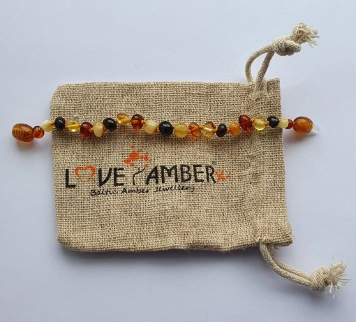 Polished mixed amber anklet laid out straight on a small hessian bag