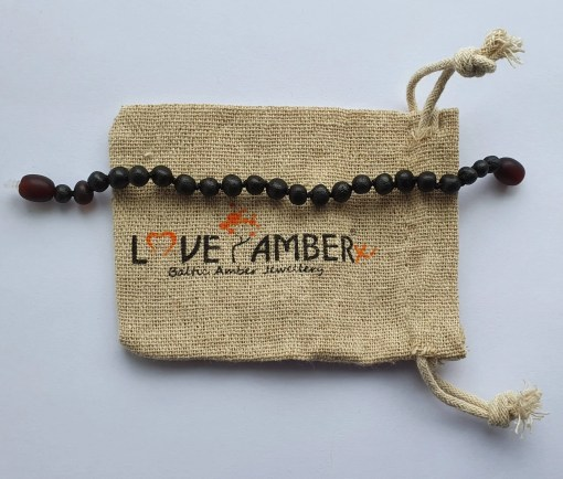 Raw dark cherry amber anklet laid out straight on a small hessian bag