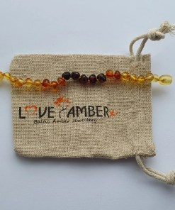 Polished rainbow amber anklet laid out straight on a small hessian bag