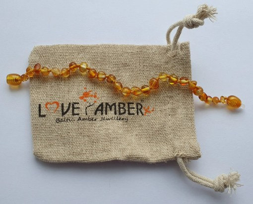 Polished honey amber anklet laid out straight on a small hessian bag