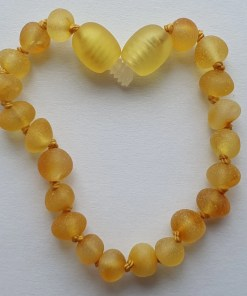 Raw honey amber anklet arranged into a heart