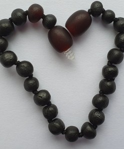 Raw dark cherry amber anklet arranged into a heart