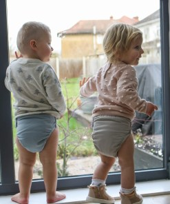 Two toddlers looking out of a glass door wearing Close Pop-in Nappies in Sky and Cloud