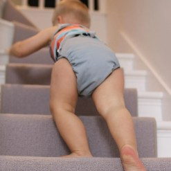 Toddler climbing stairs wearing Close Pop-in V2 nappy in Slate