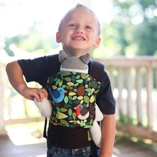 Smiling toddler wearing a doll sling