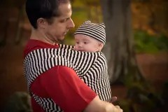 Man holding baby in a stripy mono stretchy wrap