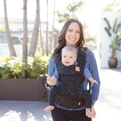 Woman carrying baby world facing in a black star print sling