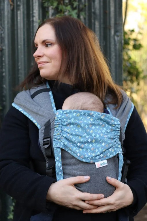 Woman carrying baby in a grey and blue buckle carrier with wrap straps