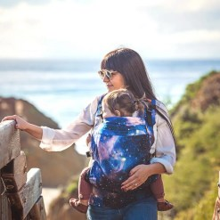 Woman carrying a toddler in a Beco Toddler sling with a milky way galaxy pattern (Carina Nebula)