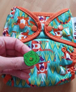 Hand holding Green Cloth Bum Mum enamel pin against a reusable nappy