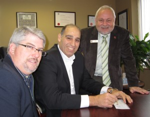 Tim Brown, left and Len Lifchus, both of the United Way,  lean just a little on Fund Raising Campaign Chair Karmel Sakran, center, to write a cheque for the amount to got the total to $2,200,00 - a record for Burlington.