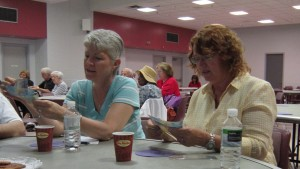 A table with several seniors looks closely at paper bills given to them to inspect.  They were asked to decide if the money was counterfeit – none of it was.