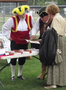 Dave Vollick, his wife and a War of 1812 re-enactor look over some material.  Vollick was acclaimed as Burlington's Town Crier for the next four years.