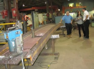 General Manager Scott Stewart with Deb Franke of AJ Braun and Craig Stevens discuss the welding of beams for the Pier. The progress schedule is top of mind for all three. One of the beams being welded is shown.
