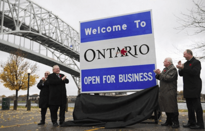 Open for business sign at border