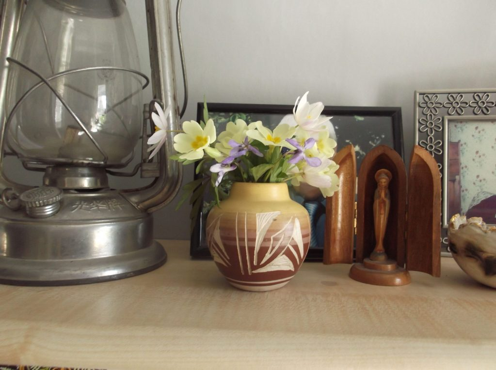 a shelf with primroses, an oil lamp and a statue of the Virgin Mary