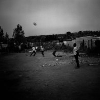 Children play football in the streets at dusk