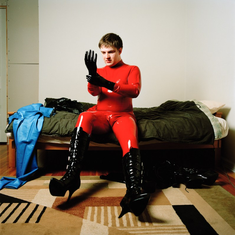 Greg dressed up in his full body red latex suit and knee high black high-heel boots. Brooklyn, NY