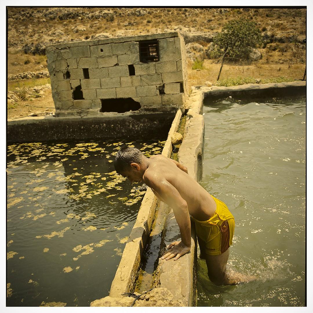 Palestinian teenager bathing in the ancient farming pools of Wadi Fuqin.