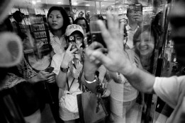 Eager fans crowd a jewelry store hoping to catch a glimpse or snap a photo of a popular television actress as she shops at a mall in Guangzhou, China 2009.