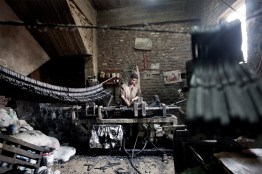 Man working in a clotheshanger's atelier. All the final products are obtained from recycled materials