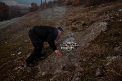 Uros Popovic lights his cigarette from the embers of a bonfire near Velika Hoca during Christmas Eve celebrations.