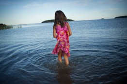 A young girl wades into Lake Athabasca, in Fort Chipewyan.