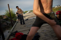A group of young boys swim off of a dock, on Lake Athabasca.