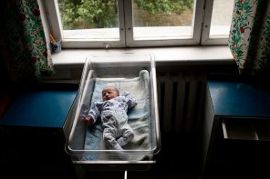 """Newborn baby Inna Hakobyan lies in her cot at Stepanakert Maternity Hospital. Her mother Narine and father Suren have received approximately €1150 (600,00 ad) in wedding and baby payments as part of the government's """"Birth Encouragement Program"""". Stepanakert, Nagorno Karabakh 2011."""