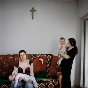 """21 year old Ani Hakobyan (b.1989) at home with her mother-in-law Maro Hakobyan and 2 of her 4 daughters. Ani and her husband Artak got married in the 2008 mass wedding and have so far received approximately €2800 ($4000) and an apartment in Stepanakert from the private businessmen who organised and funded the wedding, and a further €2680 (140,000 ad) from the government's """"Birth Encouragement Program"""" in baby payments for their triplets born in 2010. Aygestan village, Nagorno Karabakh, 2011."""