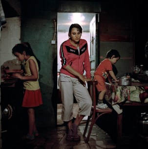 """19 year old Narine Hakobyan is pictured in the kitchen of her husbands family home with young sister-in-law, Lilit (left) and her 2 year old daughter Angelina (right). Kolatak village, Nagorno Karabakh, 2011. Narine and her husband Suren have received approximately €1150 (600,00 ad) in wedding and baby payments as part of the government's """"Birth Encouragement Program""""."""