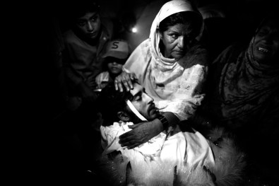 Karachi, Pakistan, September 2010: The ded body of a 20 years old men assassinated in a marked by unknown gunmen. His mather and the rest of the family is gathering around him out of the mortuary in Abbasi Shaheed Hospital to carry him at home for the funeral.