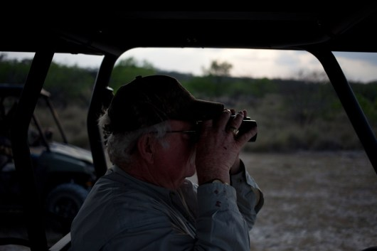 """Local landowner, Mike Vickers looks through binoculars for illegal immigrants. He and his wife started the Texas Volunteers in 2009 after they saw an increase in """"criminal trespassing,"""" on their property."""