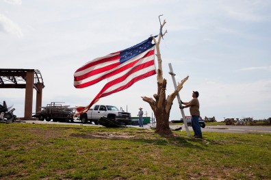 A man leans a cross upon a naked tree, next to a tattered American flag outside of a church that was destroyed by the Joplin tornado, on June 25, 2011 in Jopin, Missouri.