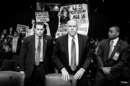 Security surrounds John Brennan as protesters disrupt the Senate (Select) Intelligence Committee hearing room shortly after he arrived for the hearing on his nomination of to be director of the Central Intelligence Agency.