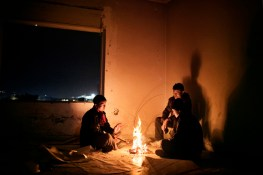 2013. Patras. Greece. Three young Afghans spend the night in an abandoned place near the beach of Patras.