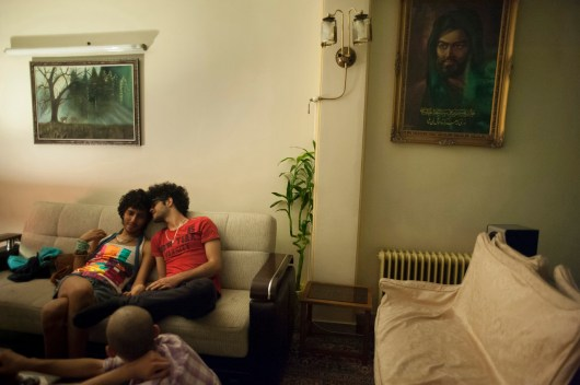 TEHRAN, IRAN - With a photo of Imam Ali, first Shi'a imam hung in the background, Sasan and Pouyan, his partner, hold hand and caress on the couch. Sasan comes from a very religious family who have been very open, accepting him as he is. Homosexuality in Islam is considered to be sin and must be penalized by capital punishment.