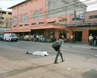Merchants in San Pedro Sula, go about their business while a body lies in the middle of the street. Dead bodies sit for hours before the coroner has time to pick them up. (Dominic Bracco II / Prime for Pulitzer Center on Crisis Reporting)