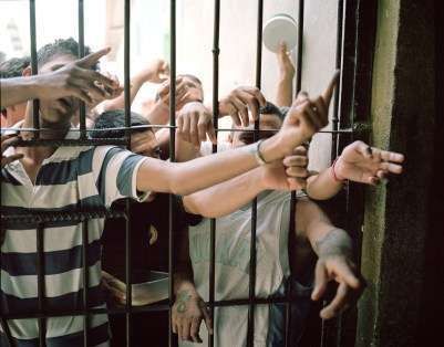Prisoners beg church members for deodorant bars in the Comayagua Prison, where three-hundred-sixty men were killed in a fire in 2012. (Dominic Bracco II / Prime for Pulitzer Center on Crisis Reporting)