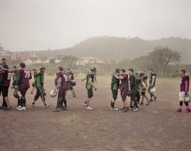 Two teams from the Honduran National American Football League congratulate each other in the rain after a game. (Dominic Bracco II / Prime for Pulitzer Center on Crisis Reporting)