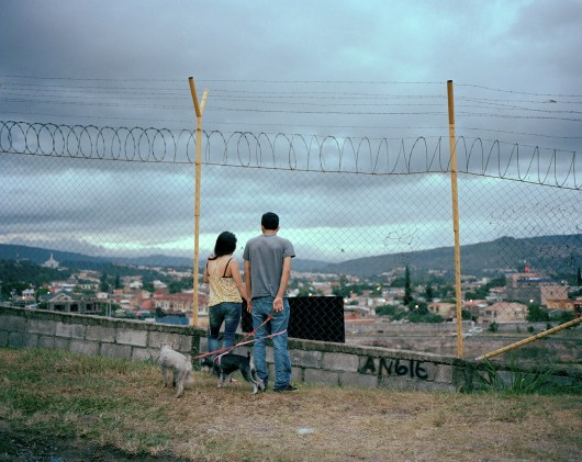 Jorge and Emilia watch planes take of from the Tegucigalpa airport. (Dominic Bracco II / Prime for Pulitzer Center on Crisis Reporting)
